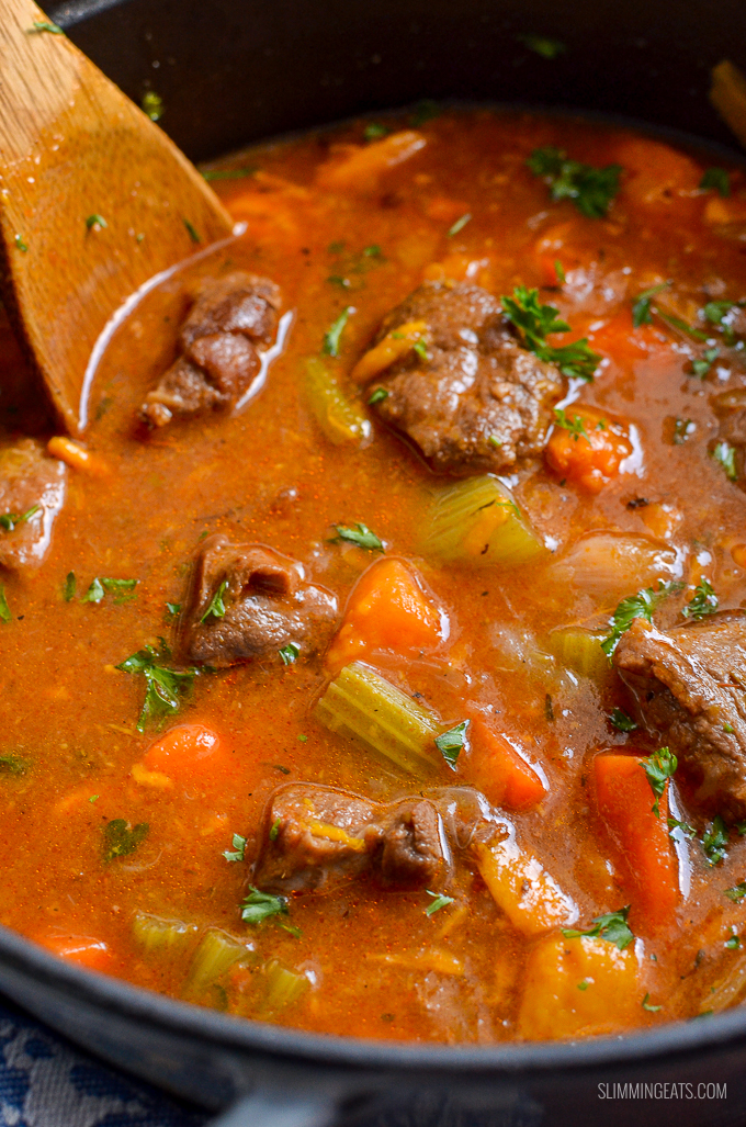 close up of beef and sweet potato stew in cast iron pot with a wooden spoon