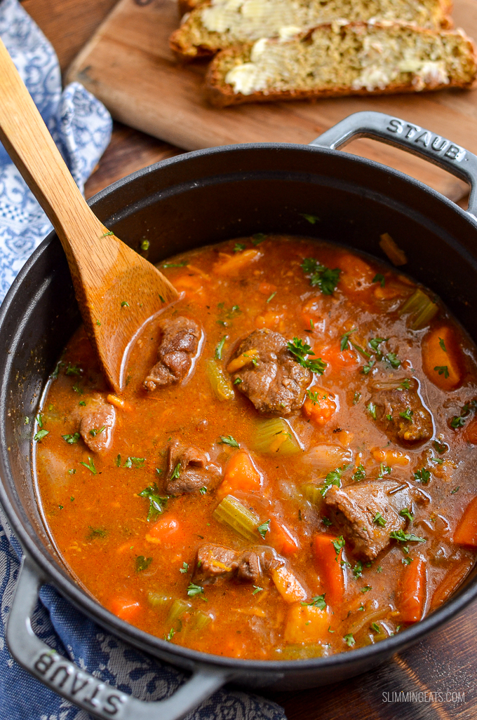 beef and sweet potato stew in a cast iron pot with wooden spoon
