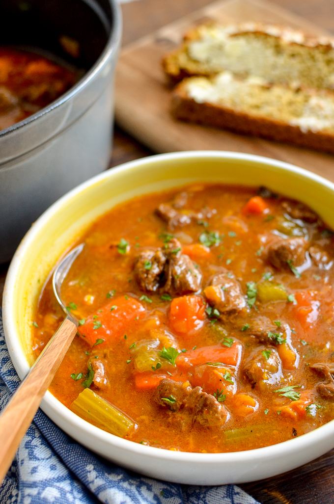 beef and sweet potato stew in a white and yellow bowl with spoon, soda bread behind on board