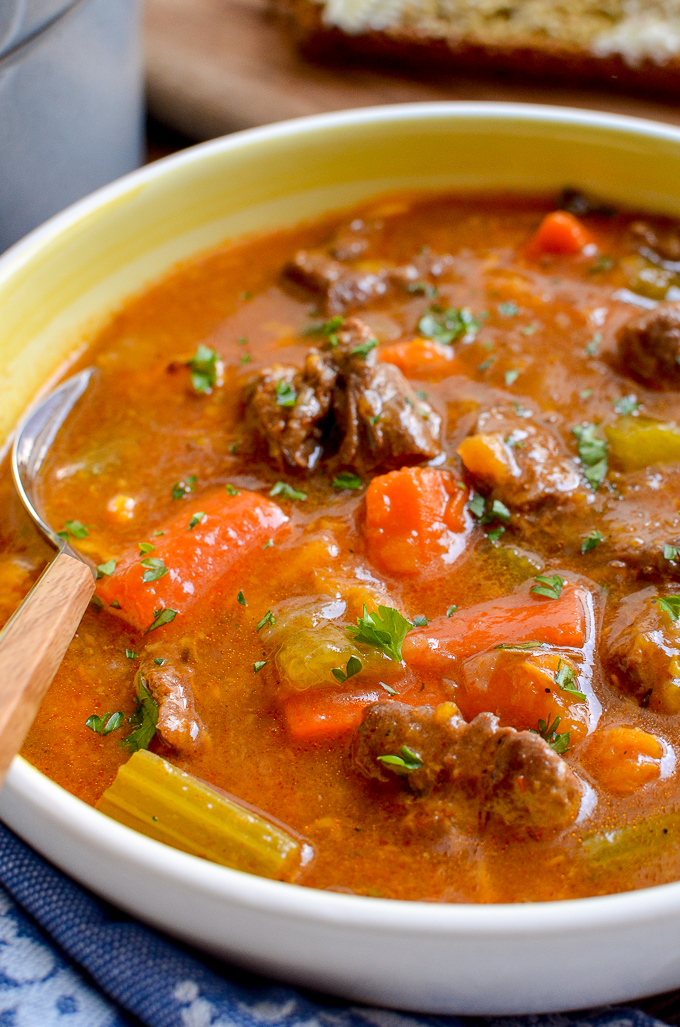 close up of beef and sweet potato stew in a white and yellow bowl