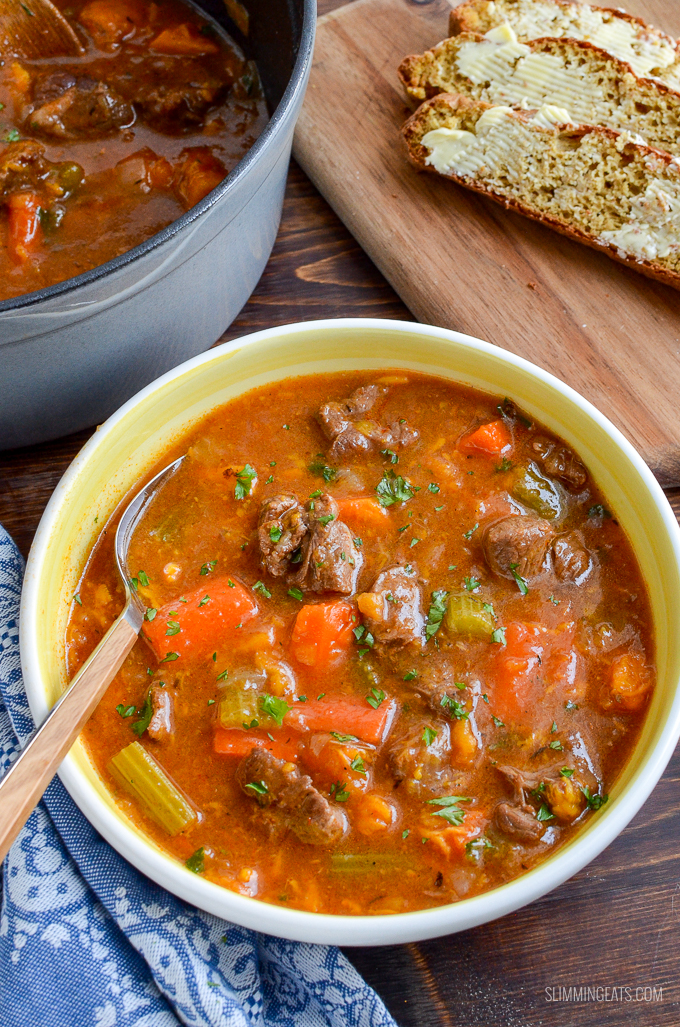 beef and sweet potato stew in a white and yellow bowl with spoon