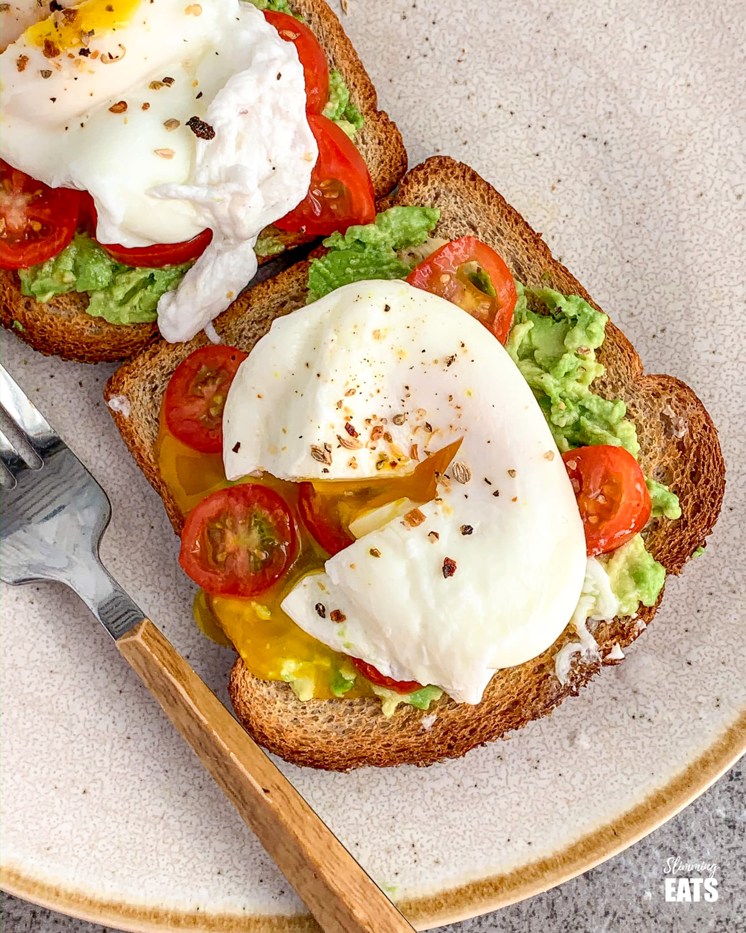 poached eggs over wholewheat toast with mashed avocado and sliced cherry tomatoes on beige rimmed cream plate with fork to the let