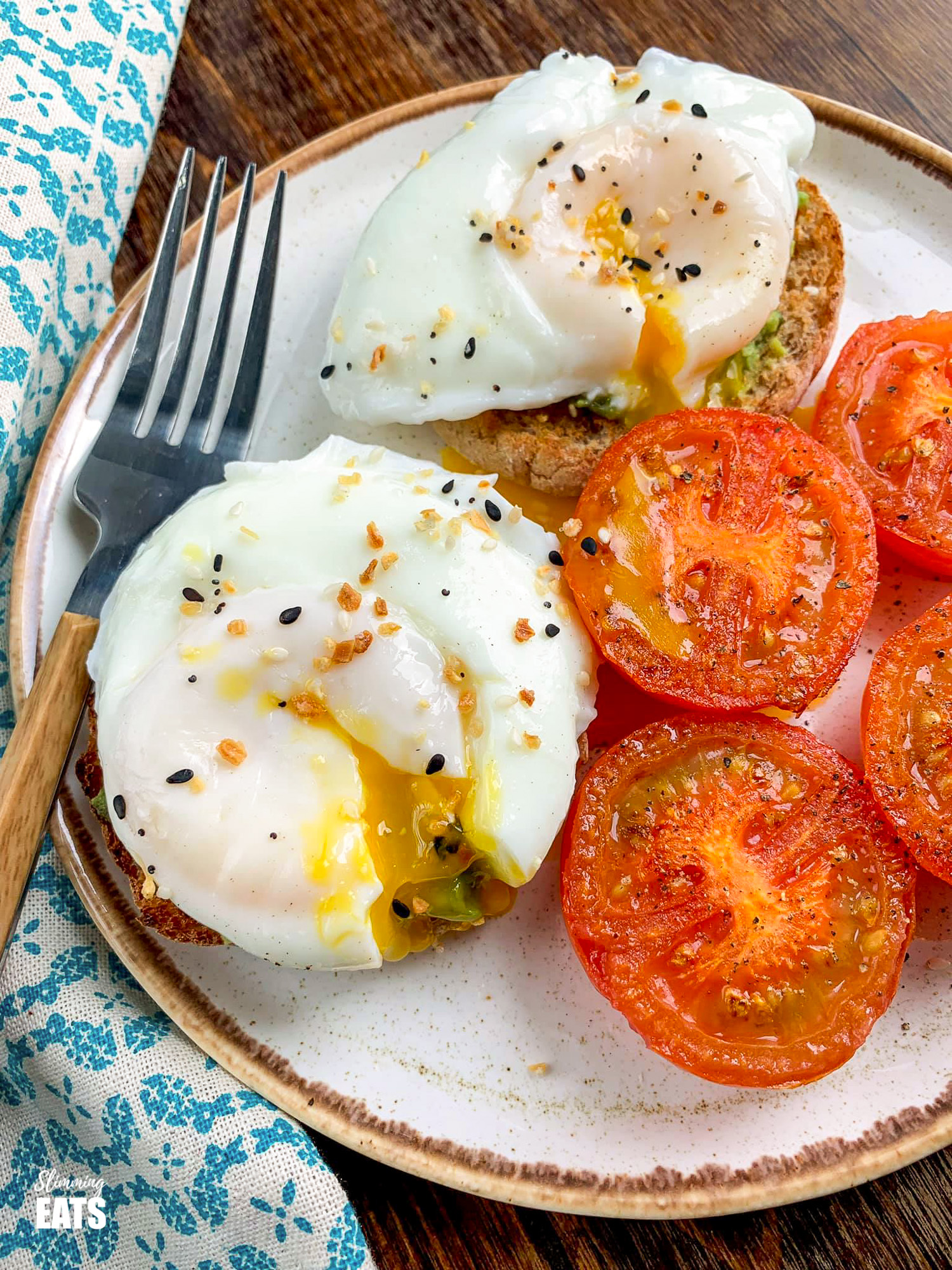 poached eggs over toasted wholewheat muffins with mashed avocado and grilled tomatoes on brown rimmed cream plate