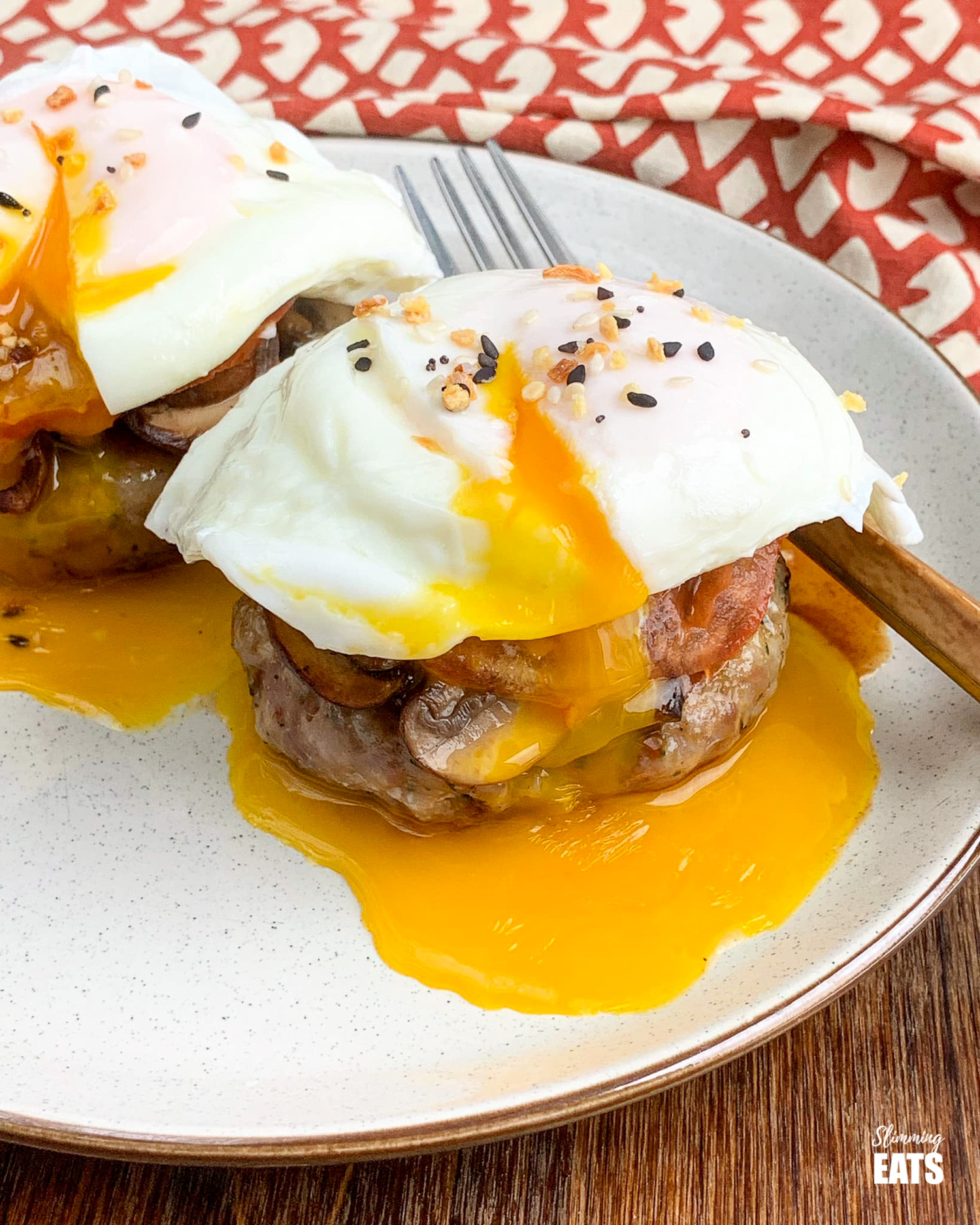 poached eggs over tomato, mushrooms and sausage patties on brown rimmed cream plate