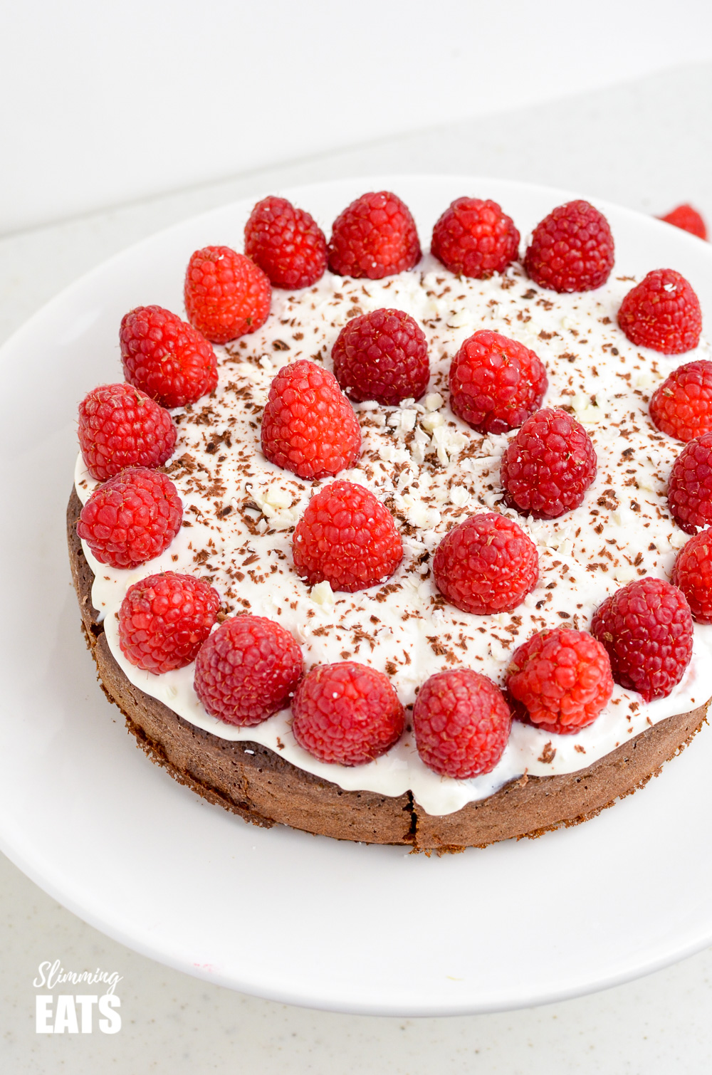 Raspberry Topped Chocolate Scan Bran Cake on white cake stand