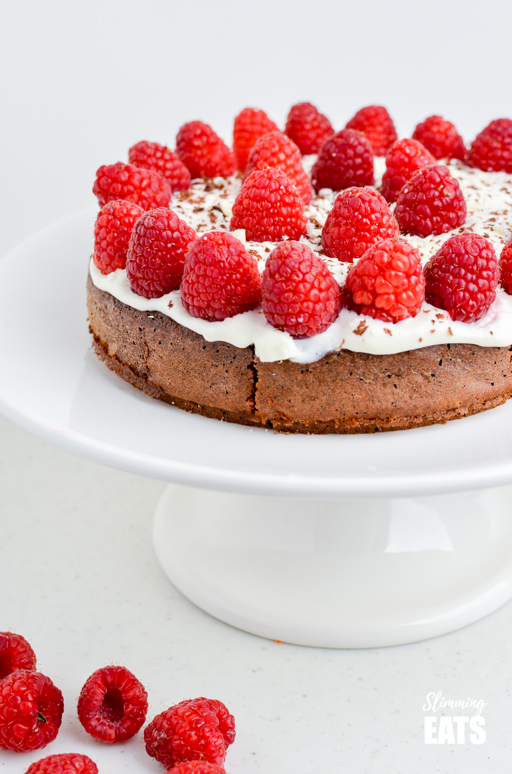 close up of Raspberry Topped Chocolate Scan Bran Cake on white cake stand