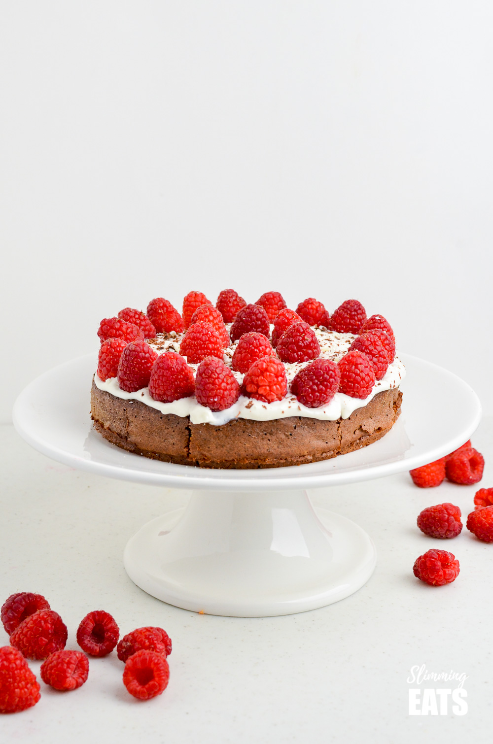 Raspberry Topped Chocolate Scan Bran Cake on a white cake stand with scattered raspberries