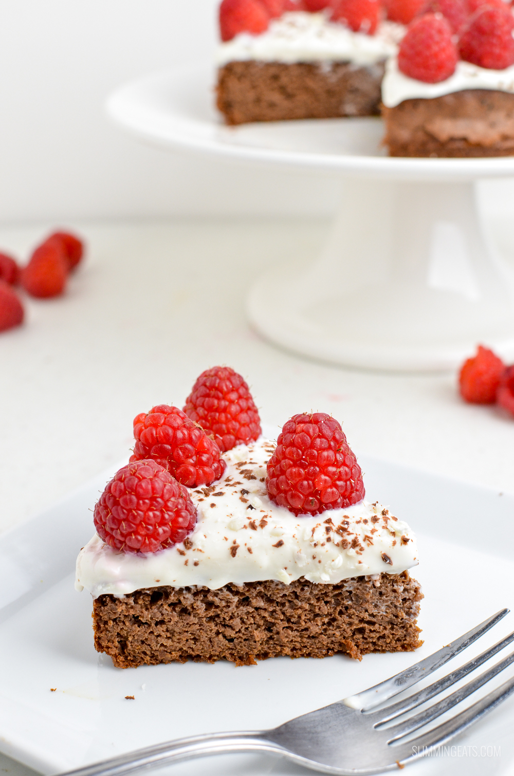 slice of raspberry topped chocolate scan bran cake on white plate with fork