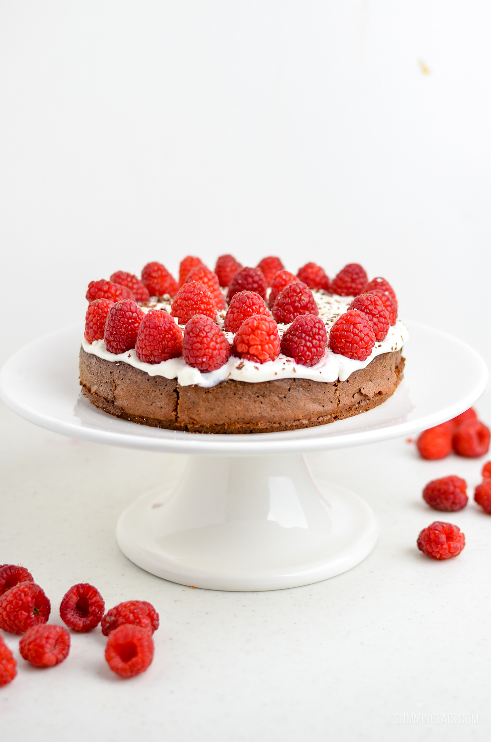 raspberry topped chocolate cake on white cake stand with scattered raspberries