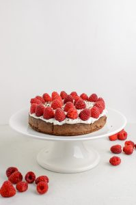 raspberry topped chocolate scan bran cake with low fat quark frosting on a cake dish with scattered raspberries