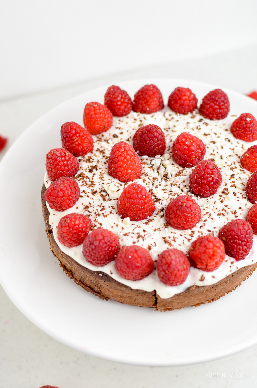 top view of raspberry topped chocolate scan bran cake on white cake stand