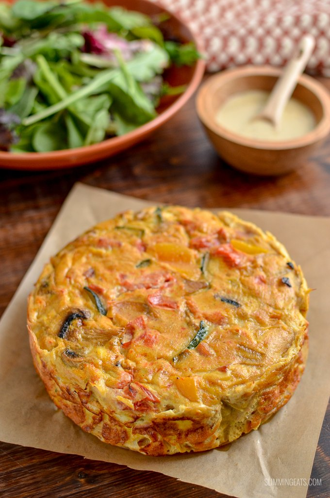 unsliced Dairy Free Crustless Bacon and Vegetable quiche on parchment with bowl of salad and dressing behind.