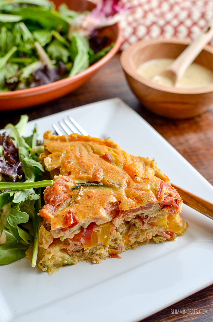 Dairy Free Crustless Bacon and Vegetable Quiche on white plate with salad and fork, dressing in wooden bowl behind