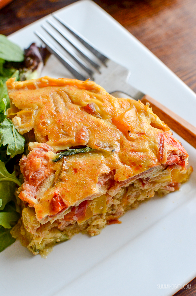 slice of Healthy Dairy Free Crustless Bacon and Vegetable Quiche on white plate with salad and fork