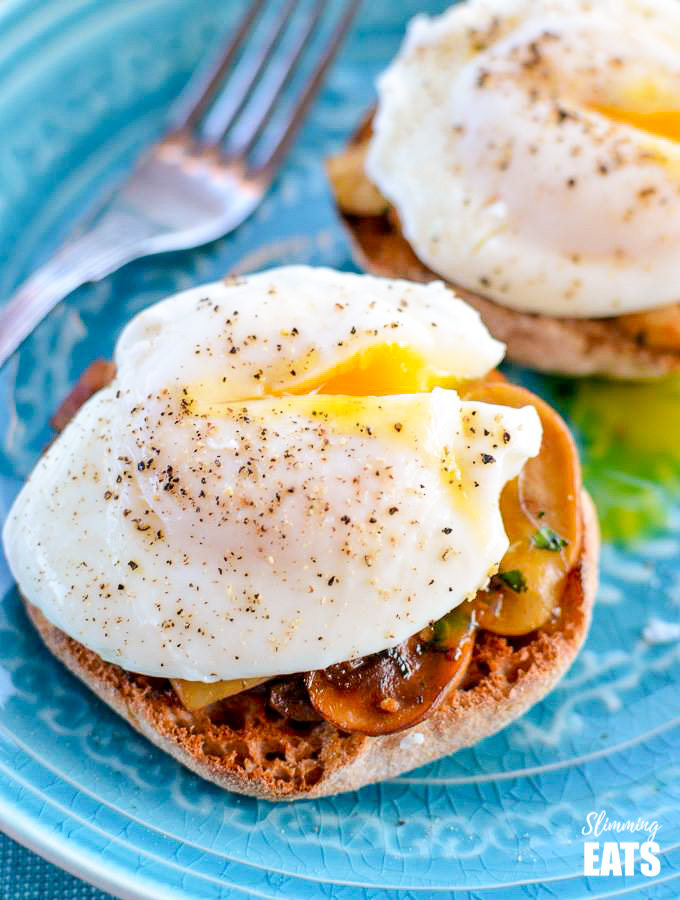 cheats poached eggs on garlic mushrooms over English muffins on blue plate