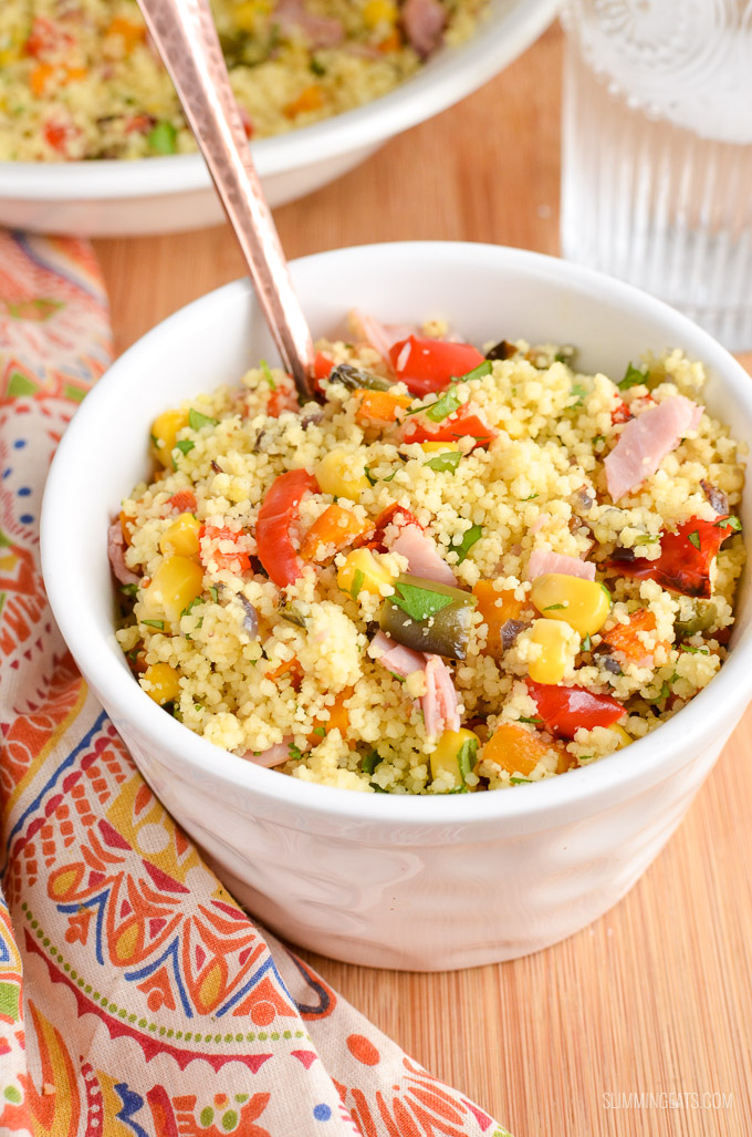 white bowl of roasted vegetables and ham couscous with spoon and patterned napkin