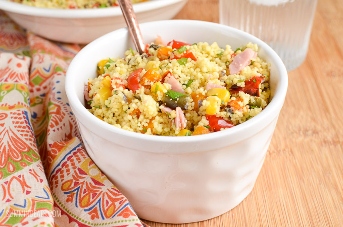 white bowl with roasted vegetables and ham couscous with spoon of wooden board with patterned napkin
