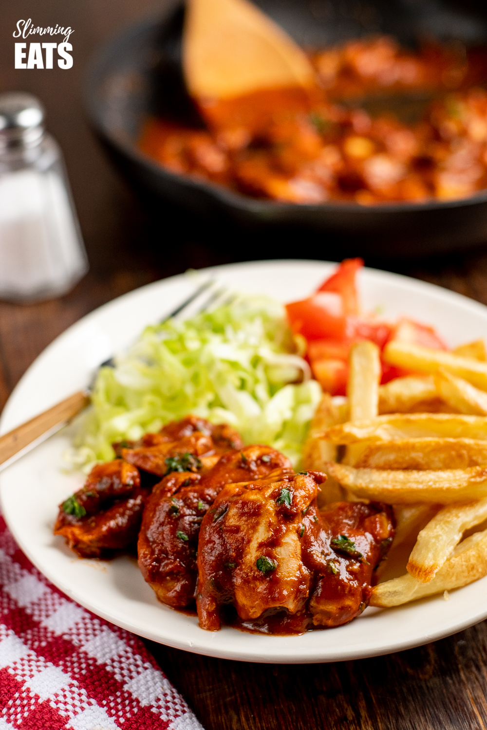 Diet Coke chicken on white plate with salad and chips and frying pan in background