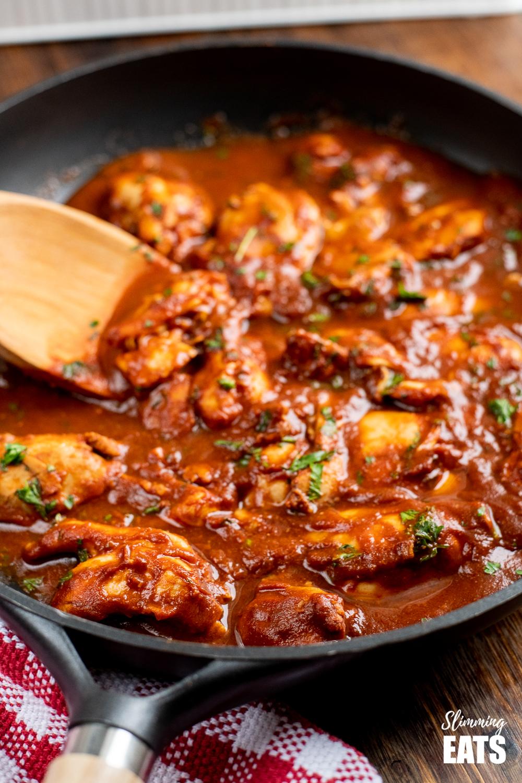 Diet Coke chicken in black frying pan with wooden spoon
