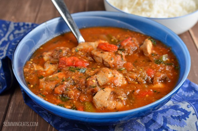 Mediterranean Chicken Chicken Casserole in blue bowl with spoon on wooden board