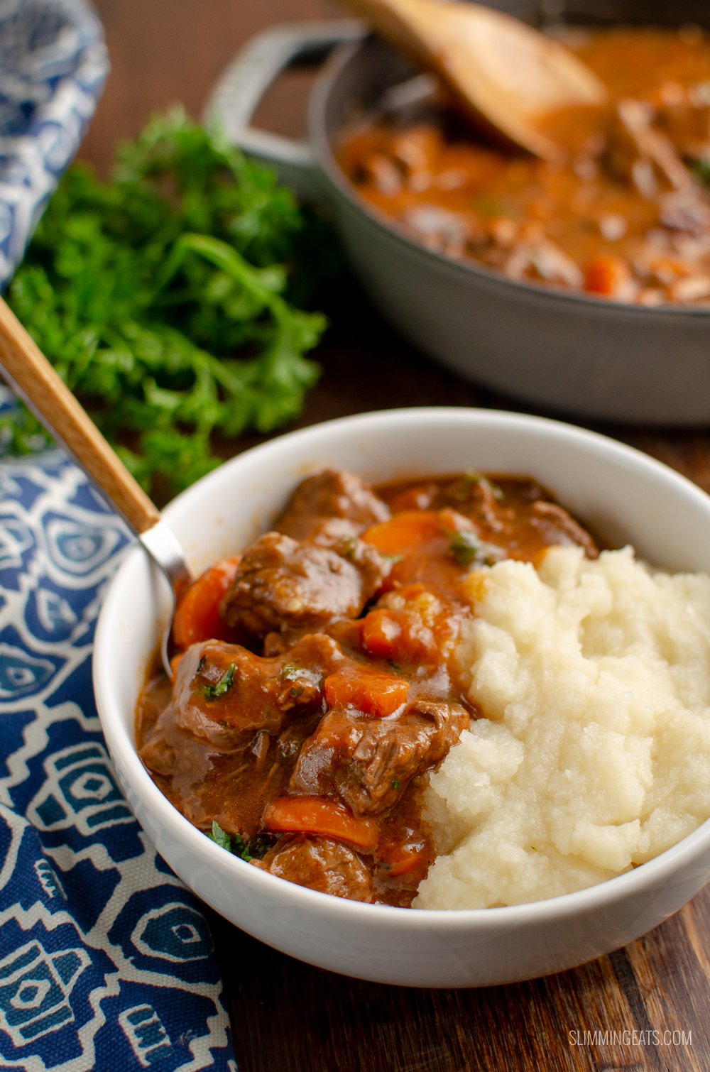 serving of low syn braised beef in white bowl served with cauliflower mash