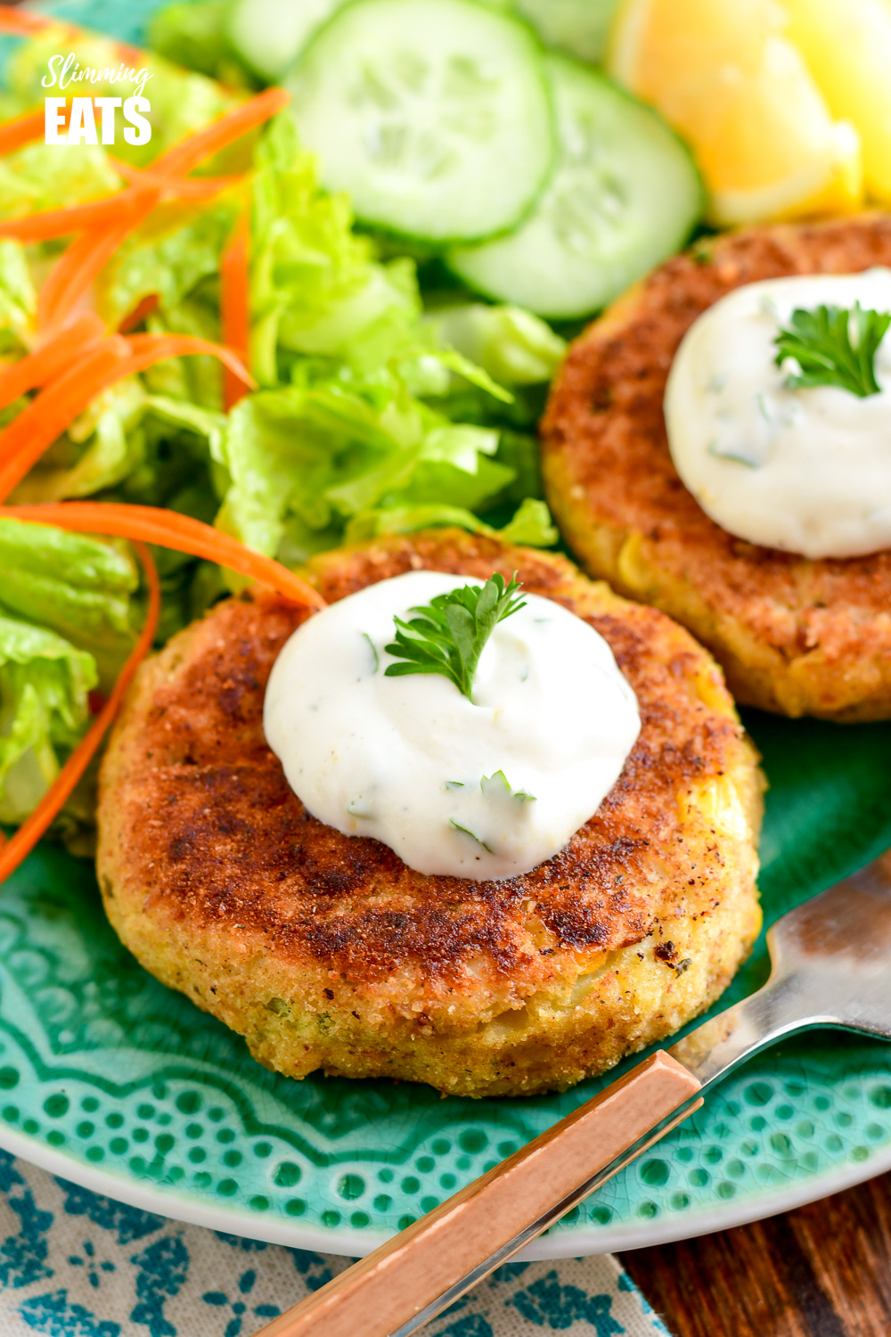 close up of low syn crab cakes with a side salad on a green plate