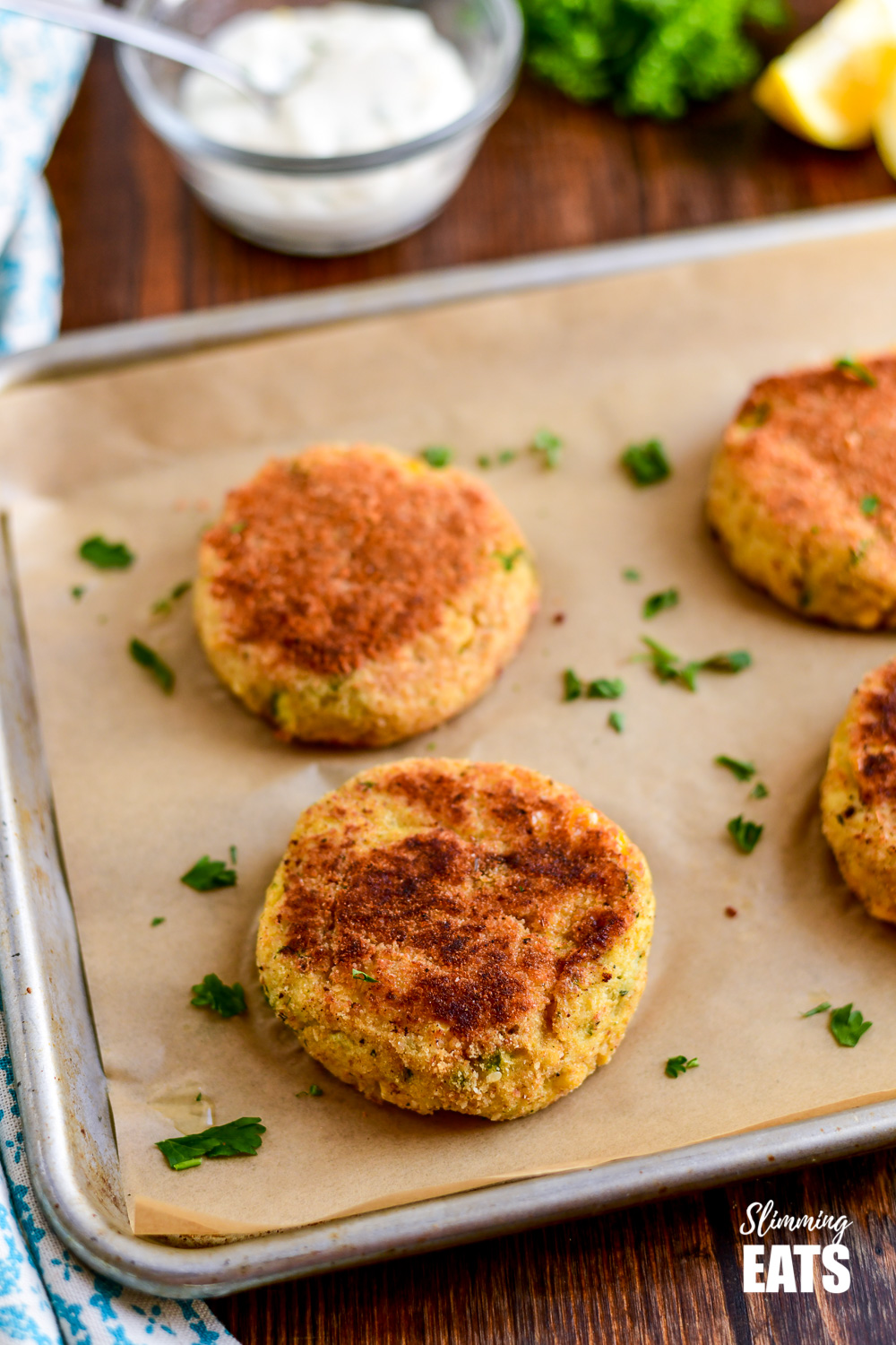 low syn crab cakes on a parchment lined baking tray