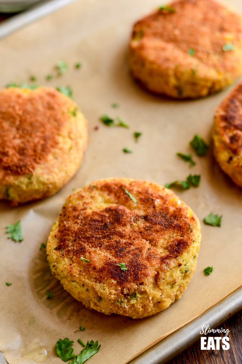 close up of low san crab cakes on a parchment lined baking tray