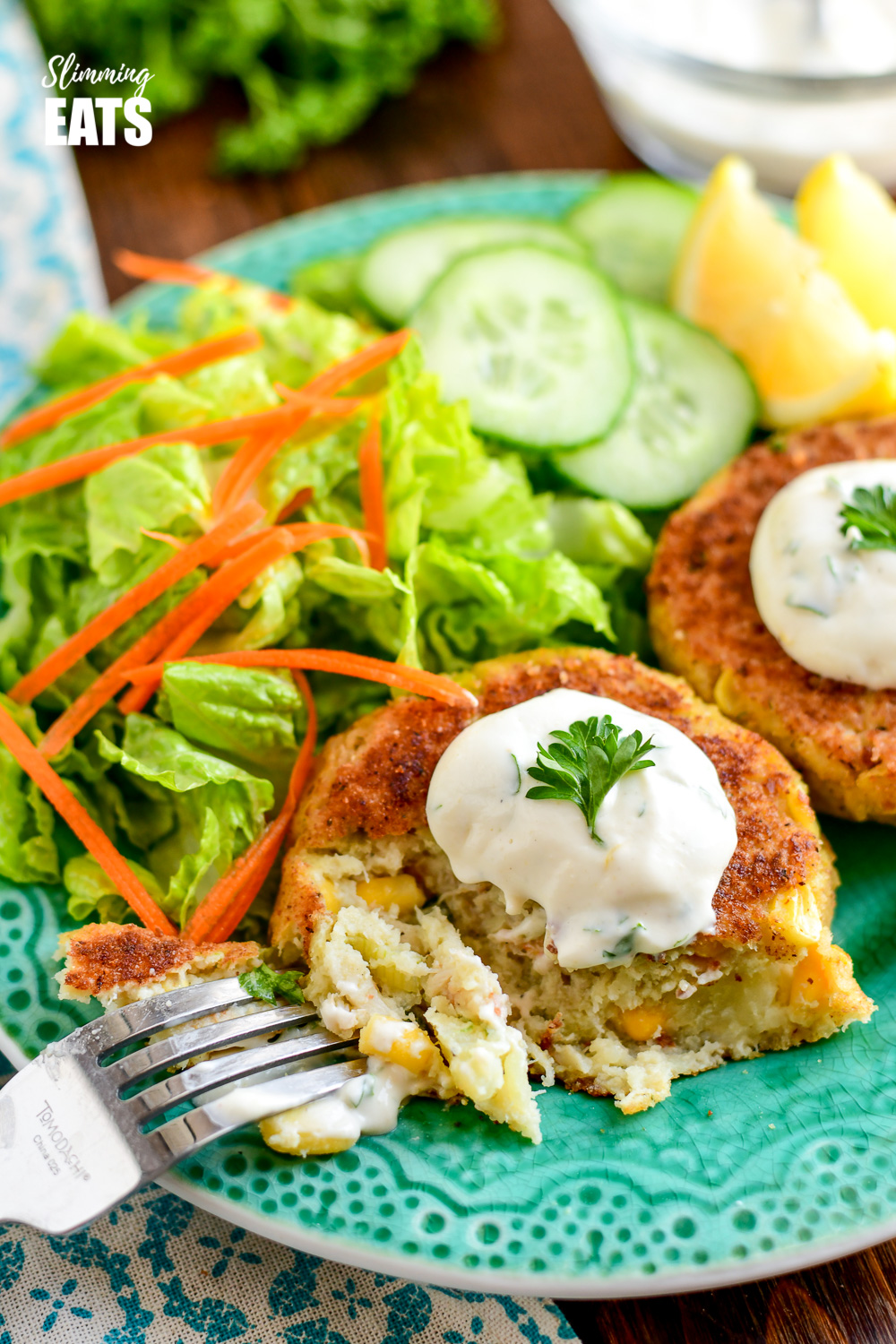 fork breaking a low syn crab cake on a green plate