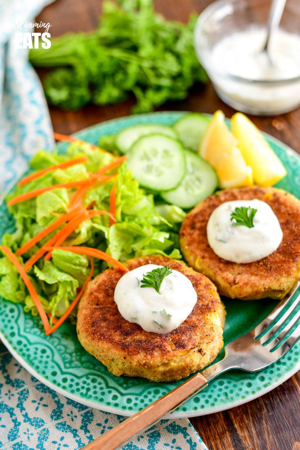 low syn crab cakes topped with dip and served with a side salad on a green plate