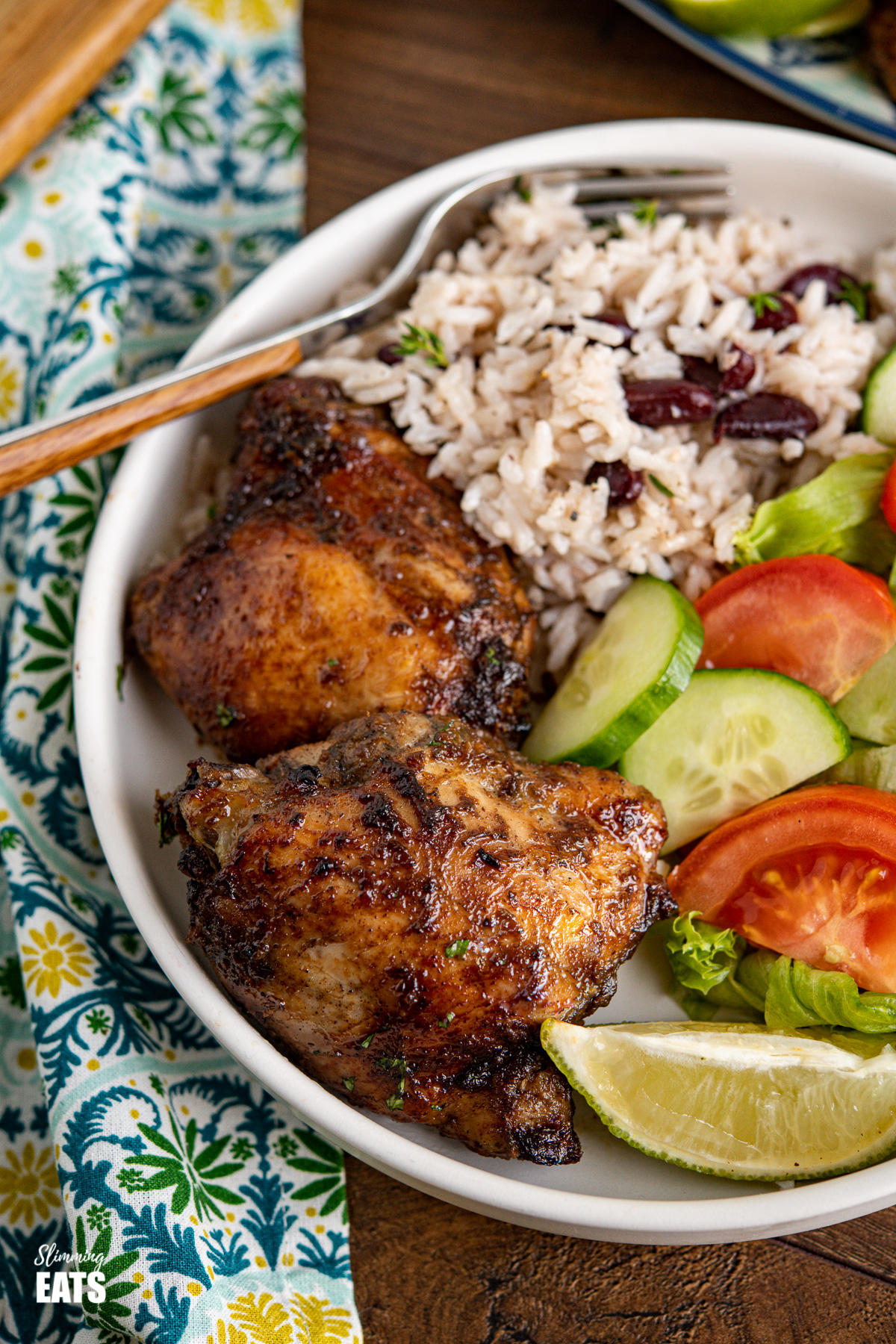close up of Jamaican Jerk Chicken with Rice and Peas in a white bowl with a lime wedge and salad