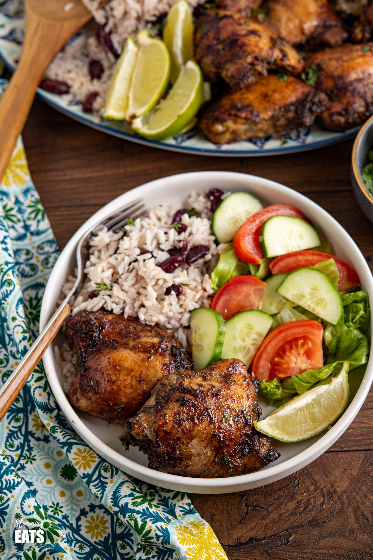 Jamaican Jerk Chicken with Rice and Peas in a white bowl with a lime wedge and salad, oval platter of jerk chicken and rice and peas in background