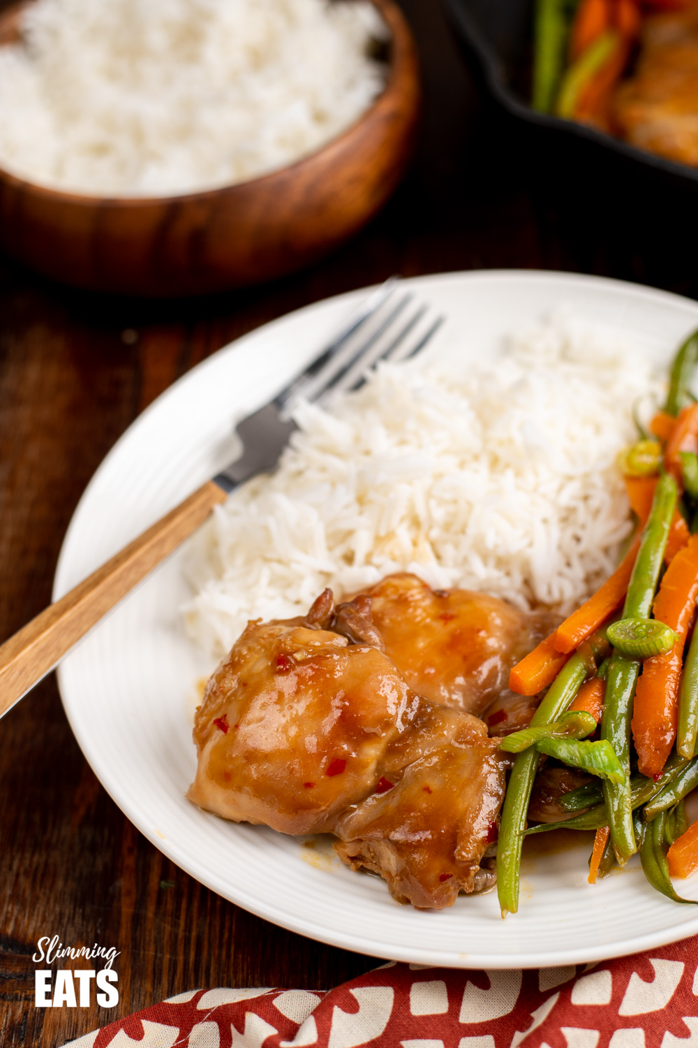 Thai spiced chicken on white plate with rice and wooden handle fork.