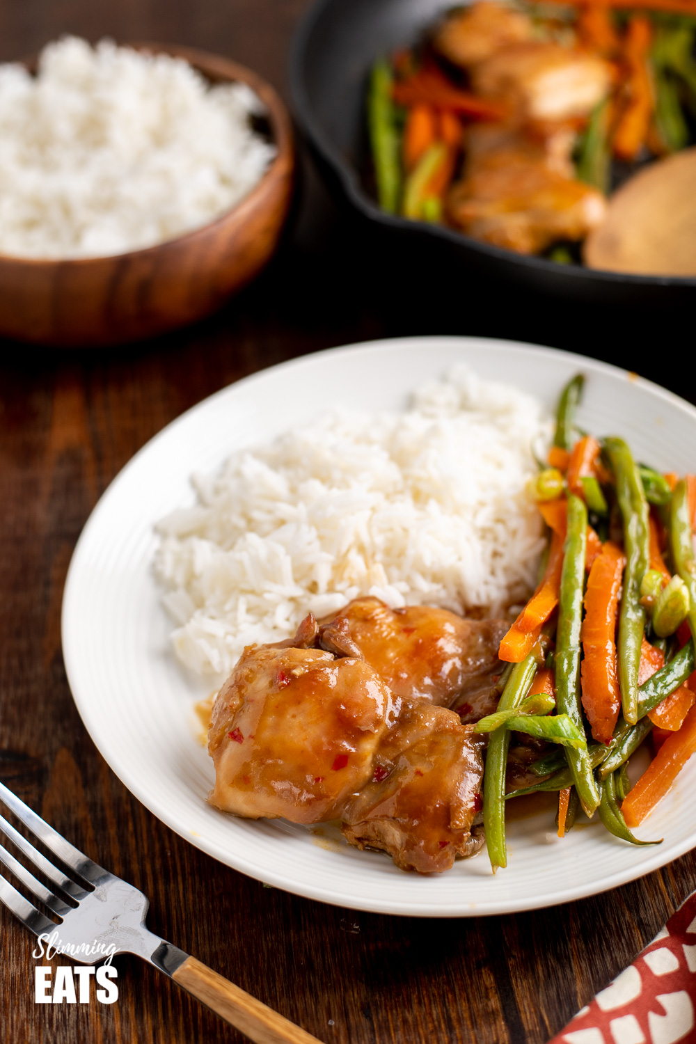 thai spiced chicken on white plate with white rice and vegetables, fork to the side and sides in background