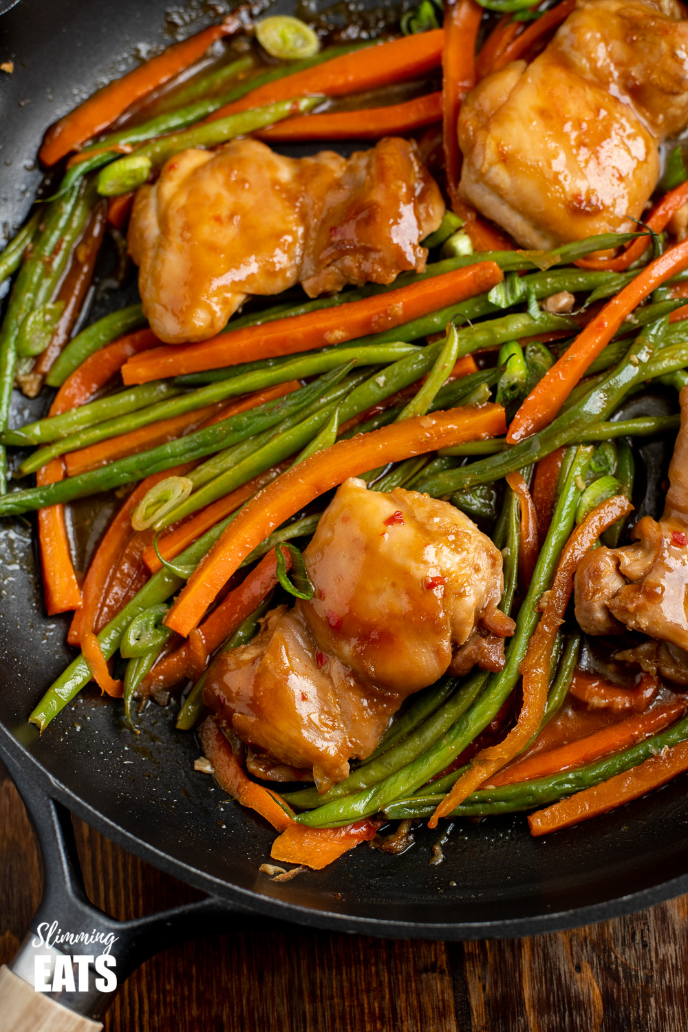 close up of thai spiced chicken in black frying pan