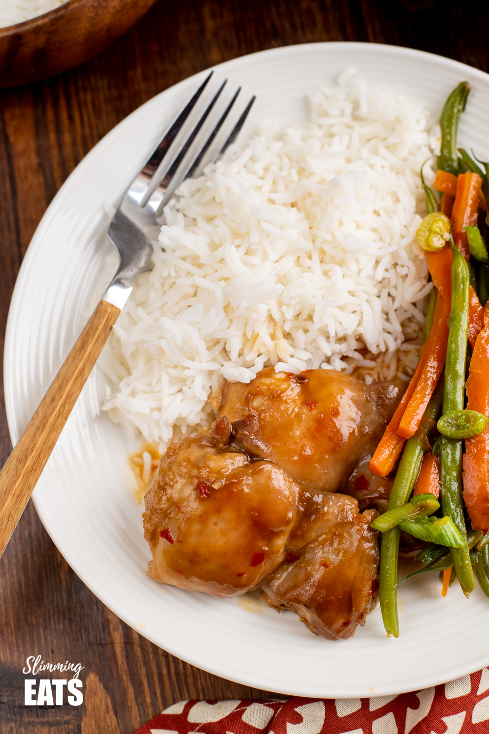 close up of Thai Spiced Chicken on white plate with rice and wooden handled fork.