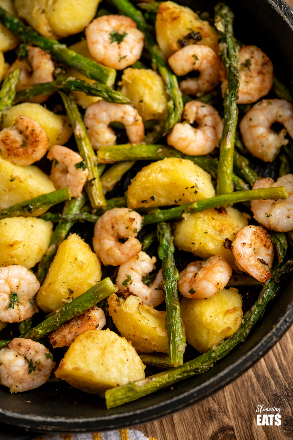 close up of warm asparagus and prawn salad in frying pan