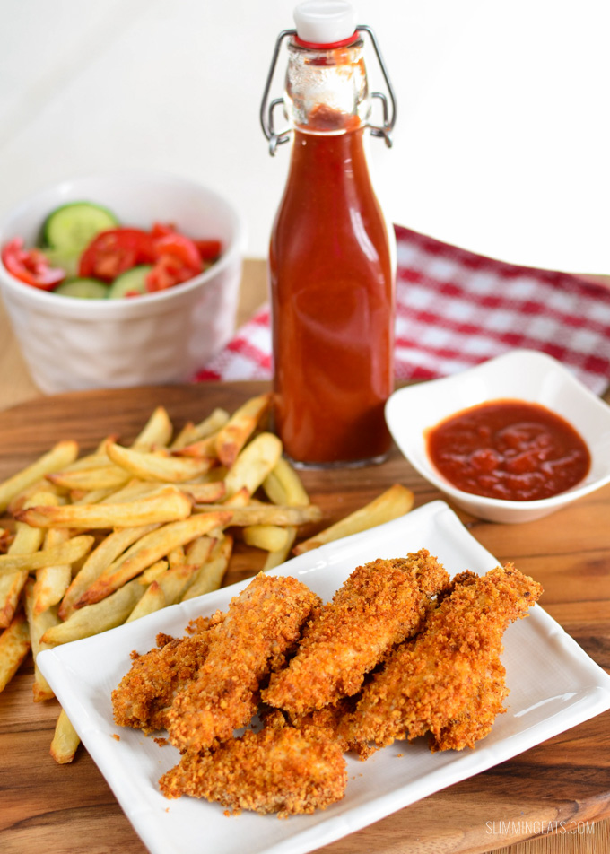 chicken fingers on white rectangle plate with sides