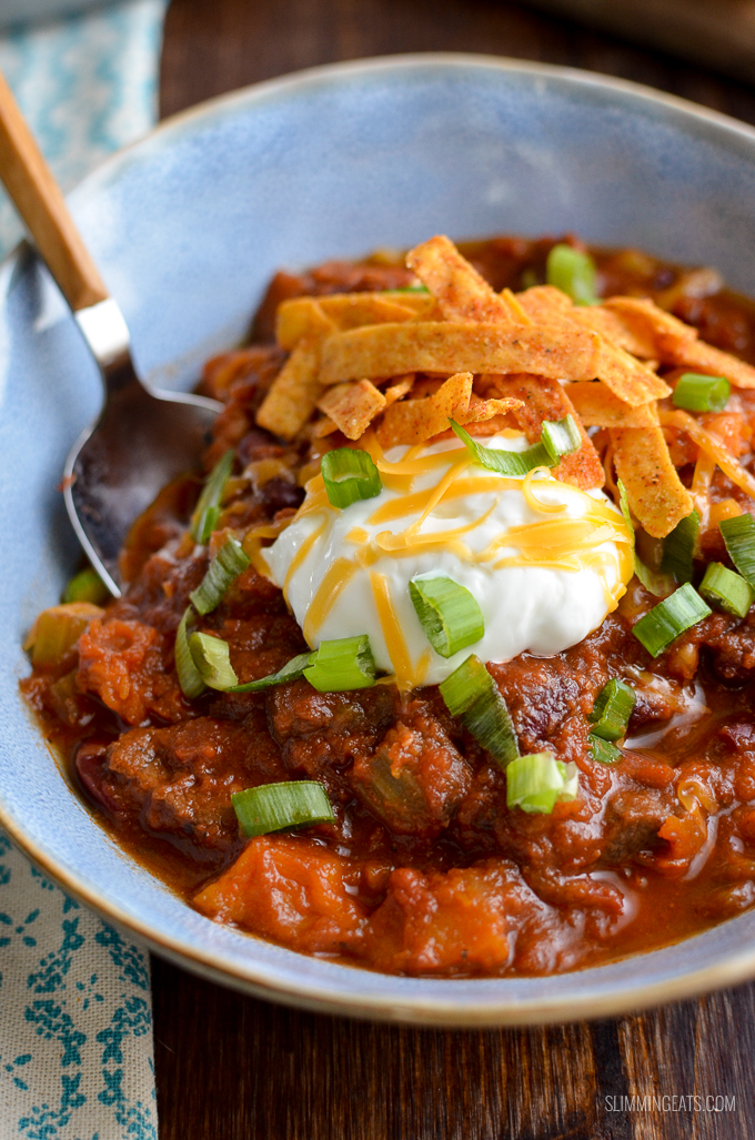 chilli in blue bowl topped with yoghurt, spring onion and tortilla strips
