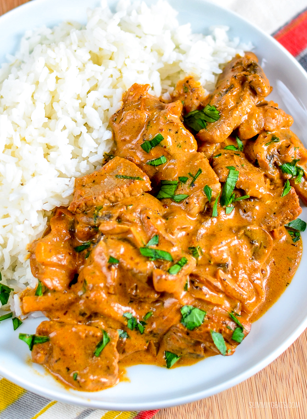 close up of beef stroganoff on a white plate with rice