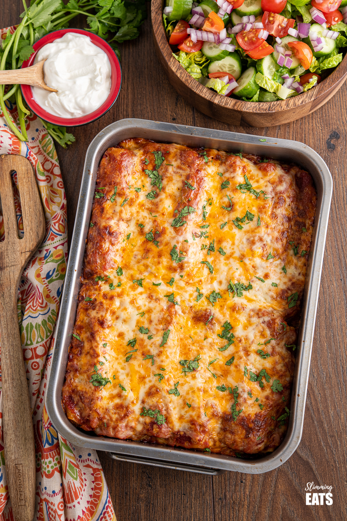 pasta chicken enchiladas in a metal baking tray with a mixed salad and soured cream in background