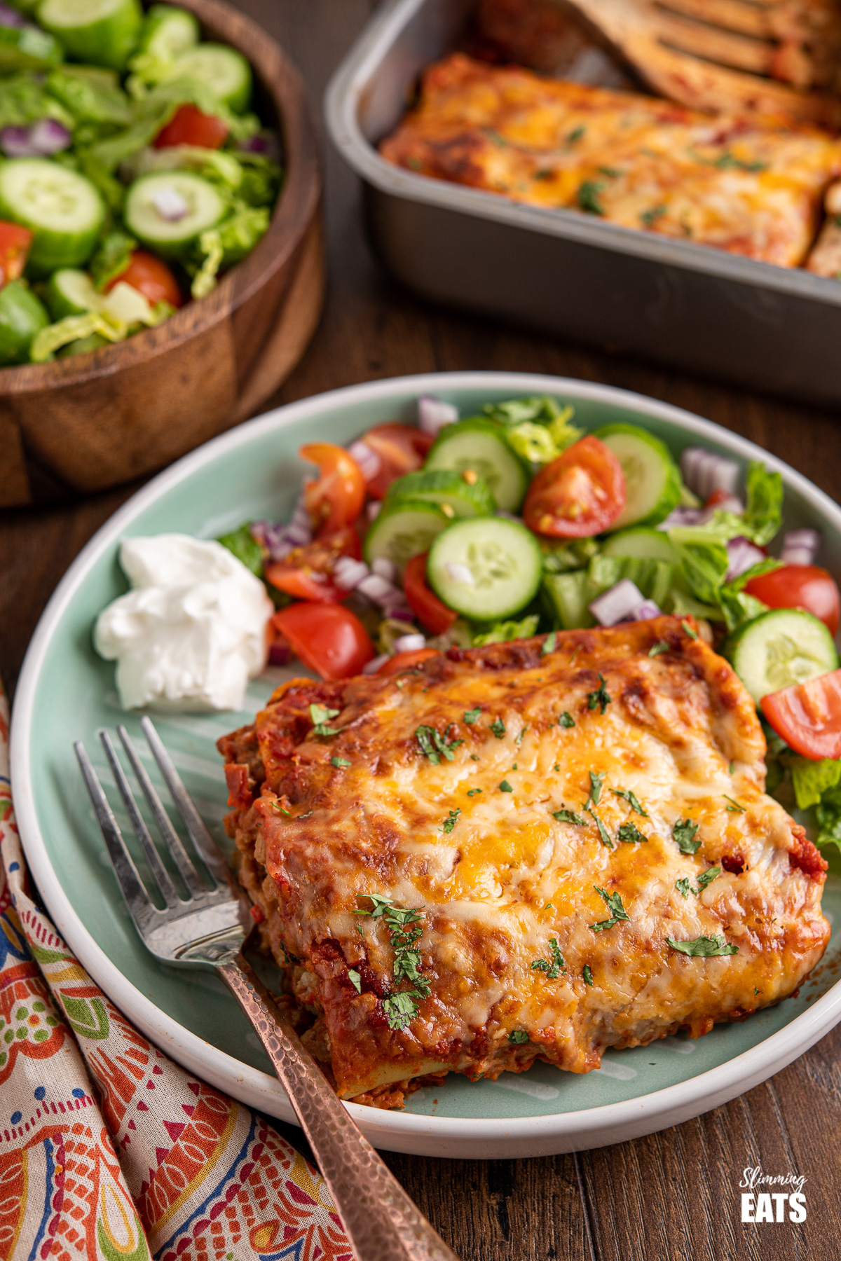 serving of pasta chicken enchiladas on a light teal plate with mixed salad and soured cream
