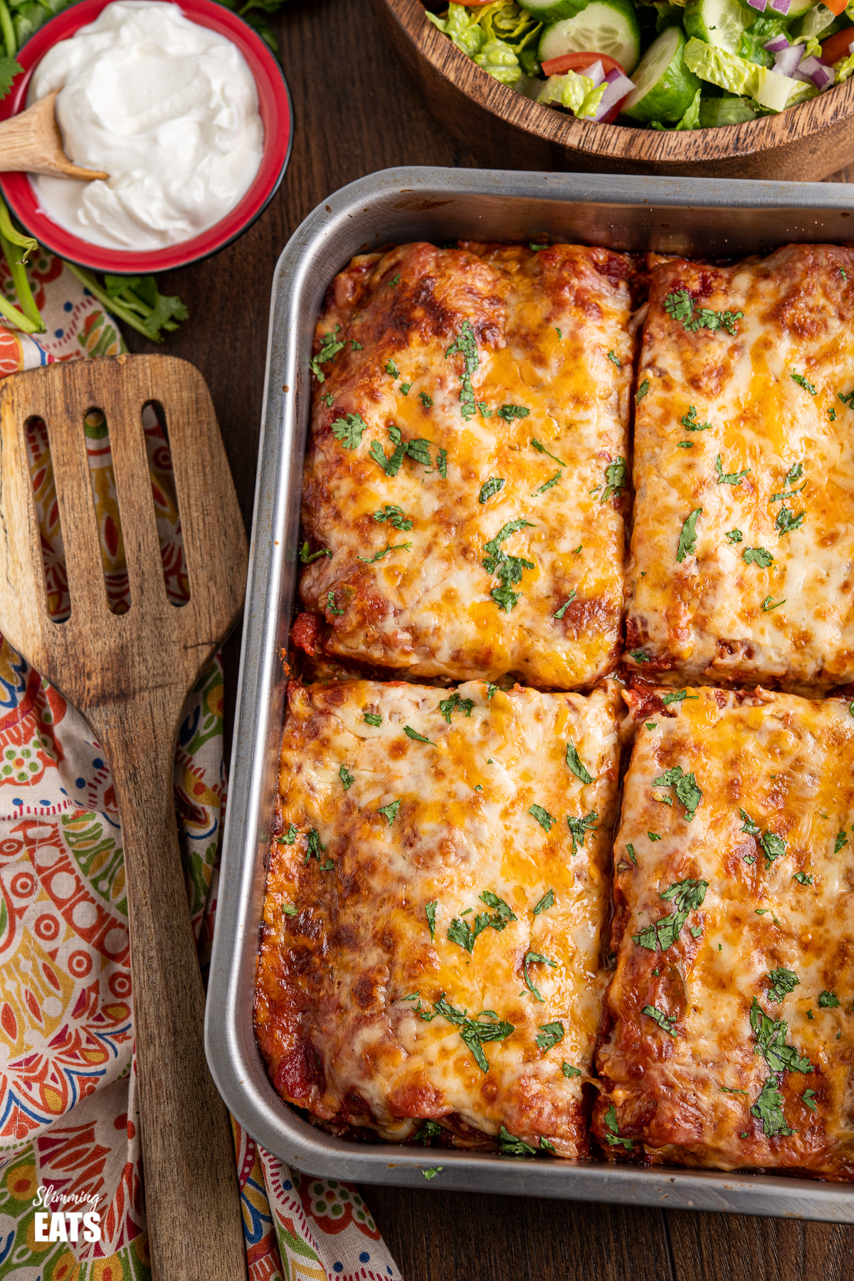 sliced pasta chicken enchiladas in metal baking tray with soured cream and salad in background