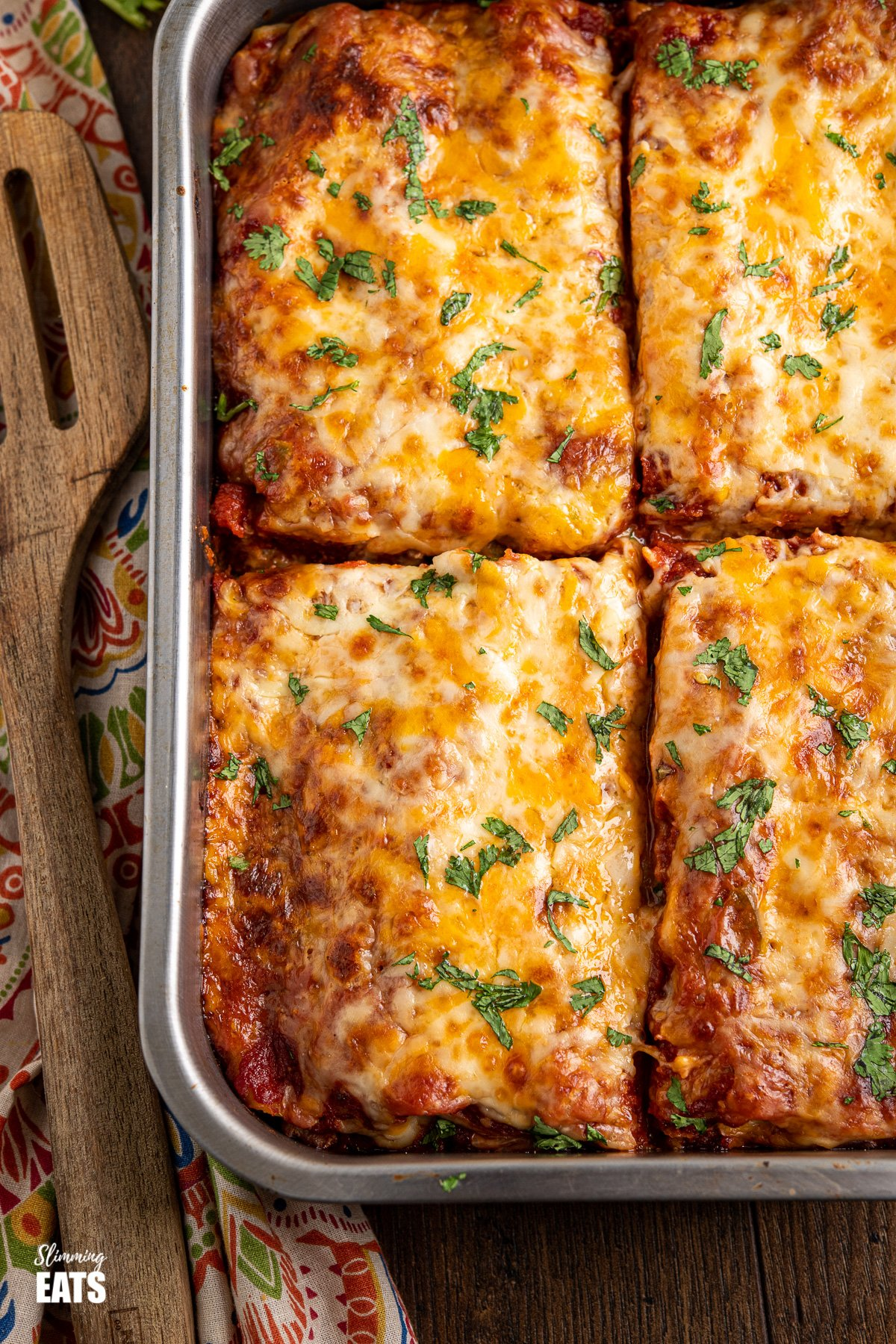close up of sliced pasta chicken enchiladas in metal baking tray