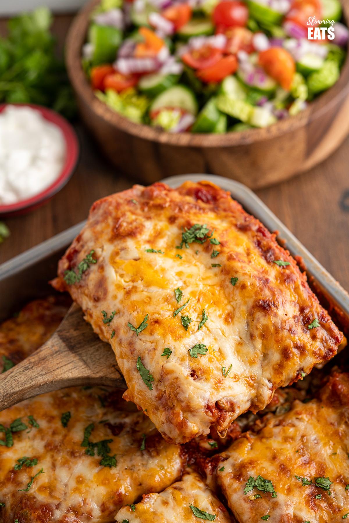 wooden spatula serving up slice of pasta chicken enchiladas from metal baking dish