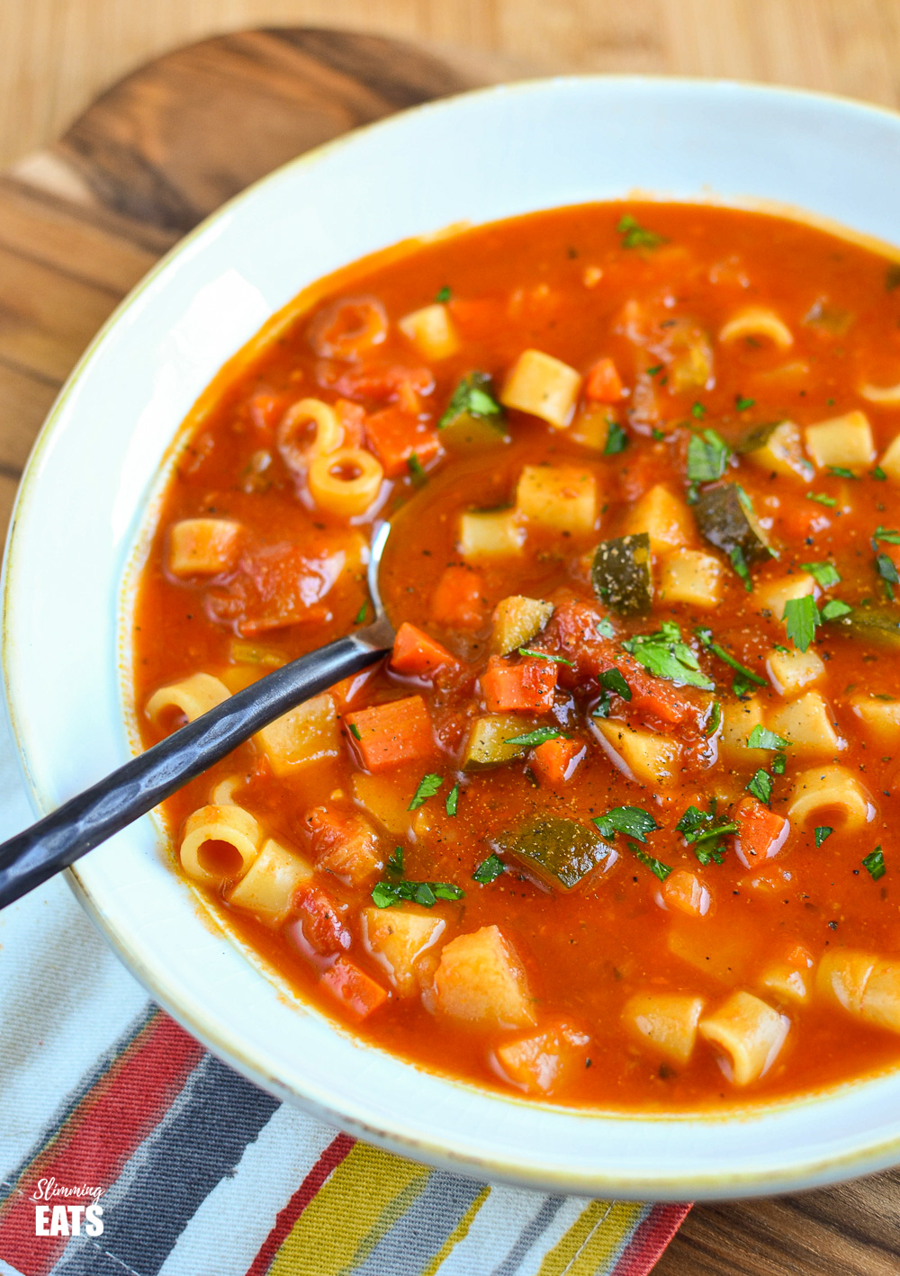 white bowl of minestrone soup with black handled spoon
