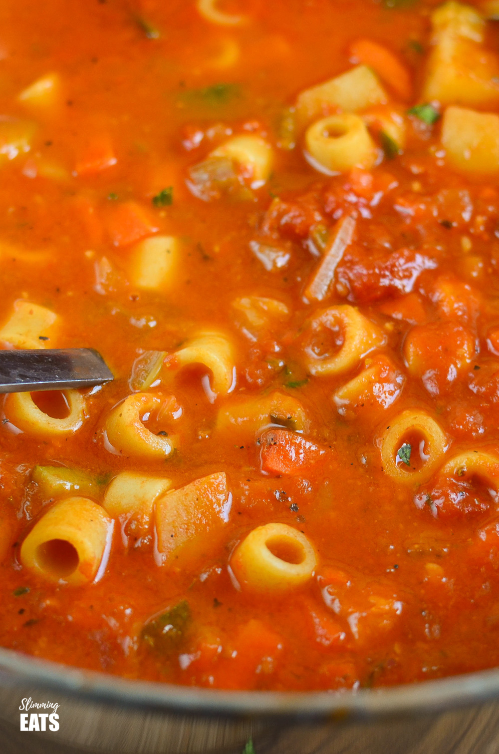close up of minestrone soup in saucepan