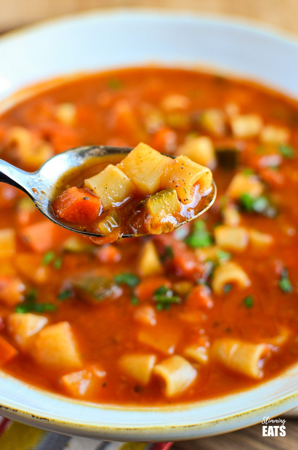 spoonful of minestrone soup from bowl