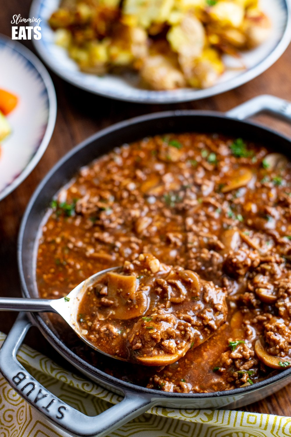 Rich Mustard Beef with Mushrooms in grey cast iron skillet