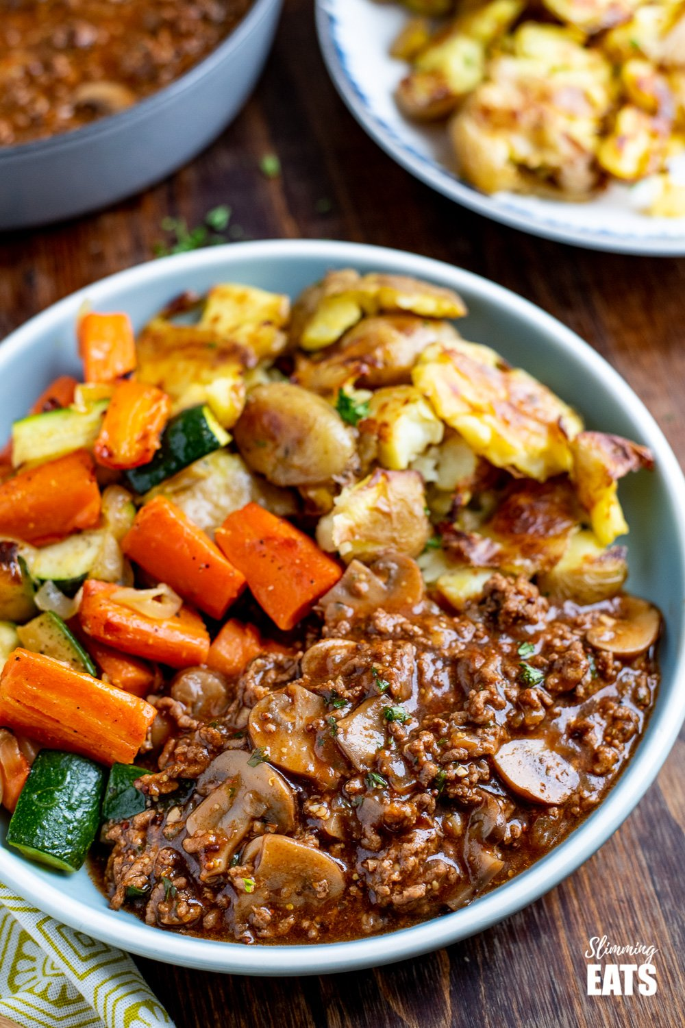 blue plate with mustard beef, potatoes and vegetables